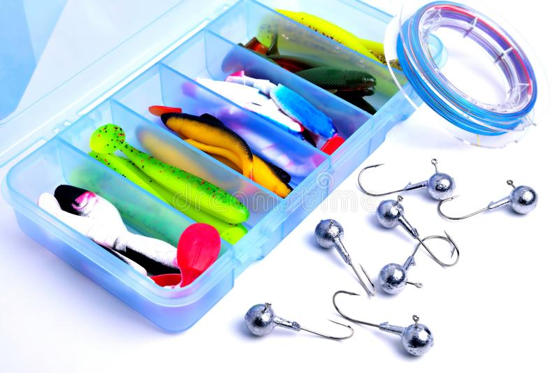 Box for fishing accessories with silicone baits inside, Jig hooks, braided reel on a white background. Close-up royalty free stock image