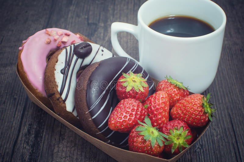 Box of fresh donuts and cup of coffee stock images