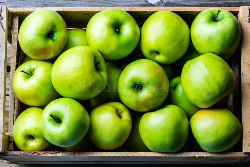 Box of fresh green apples. Harvest concept. Top view. Box of fresh green apples on wooden background. Harvest concept. Top view royalty free stock images