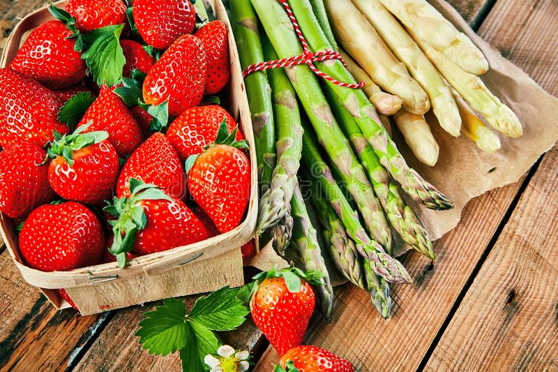 Box of fresh juicy red strawberries and asparagus stock images