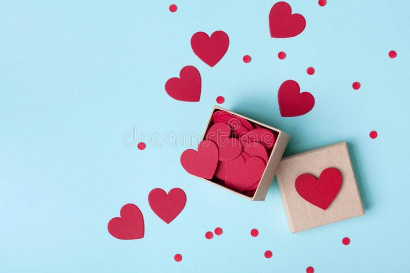 Box full of red hearts and confetti on blue table top view. Valentines day background. Flat lay style. stock images