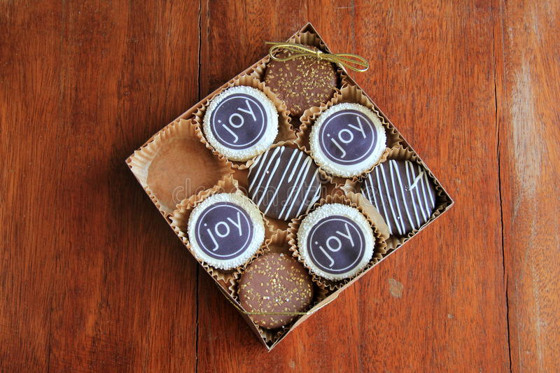 Box of gaily decorated cookies covered in chocolate. Box of eight gaily decorated cookies, covered in chocolate, sprinkles with the word 'joy' written across the royalty free stock photography