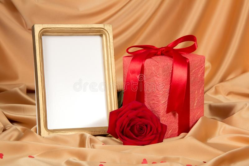 Box with gift, scarlet rose and frame for photo royalty free stock image