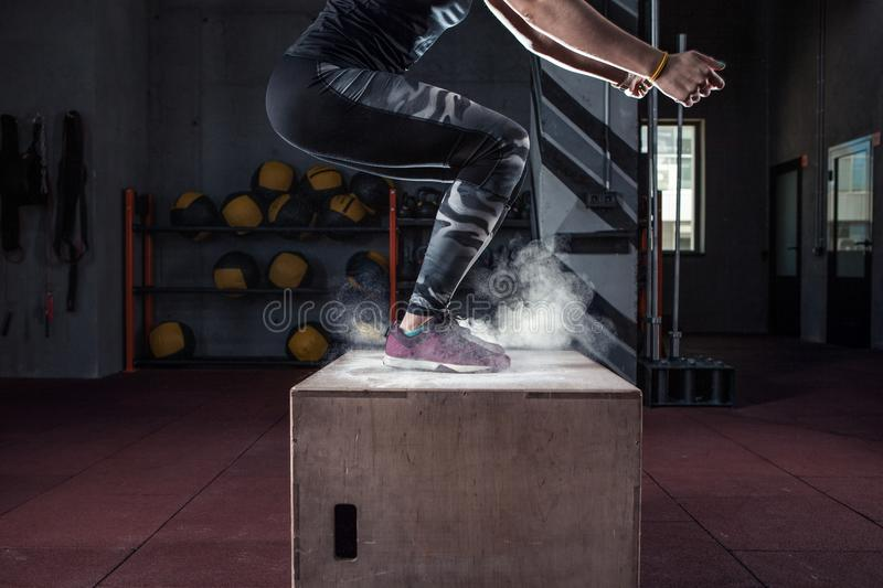 Box jump workout at cross fit gym closeup. Young woman jumping box and talc powder departs from under feet. Fitness woman doing box jump workout at cross fit gym stock photography
