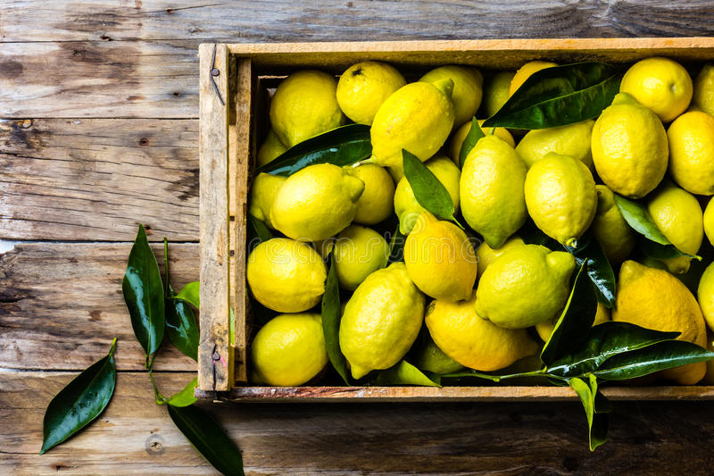 Box of lemons with fresh leaves on wooden background with copy space. Top view royalty free stock image