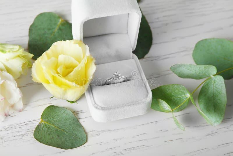 Box with luxury engagement ring. On light background royalty free stock image