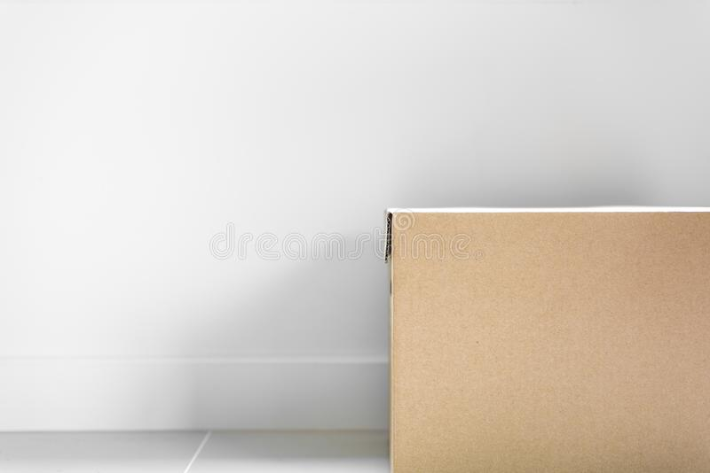 Box package parcel for post delivery on floor with grey wall background. Object and Shape concept. Mail and Post service theme. White, cube, square, carton royalty free stock photos