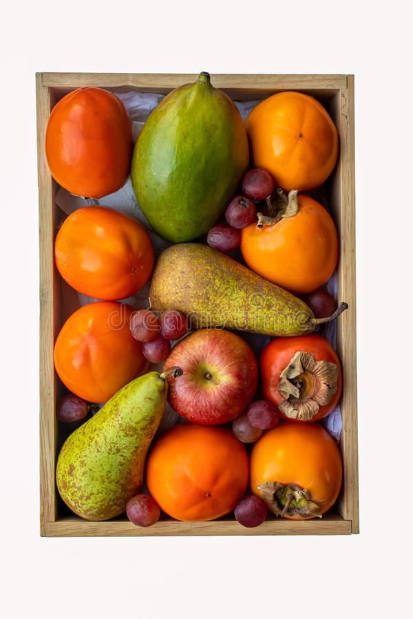 Box of persimmon and other assorted fruits stock photos