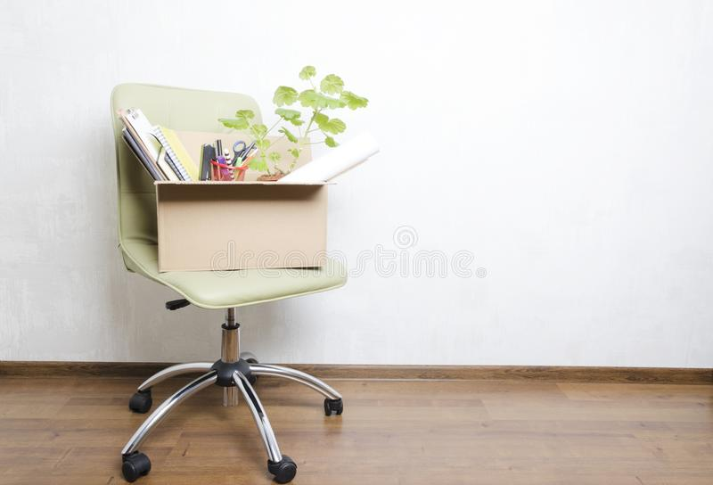 Box with personal items standing on the chair in the office.Concept of moving or dismissal. Vertical shot.Box with office stationary.green chair, blank speech stock photo