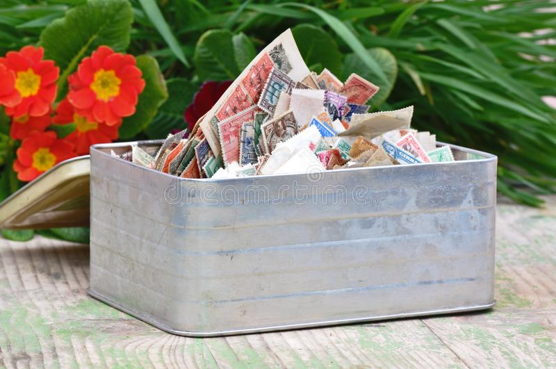 Box with pile of stamps. Pile of stamps collection on a metal box with colored natural background royalty free stock photo