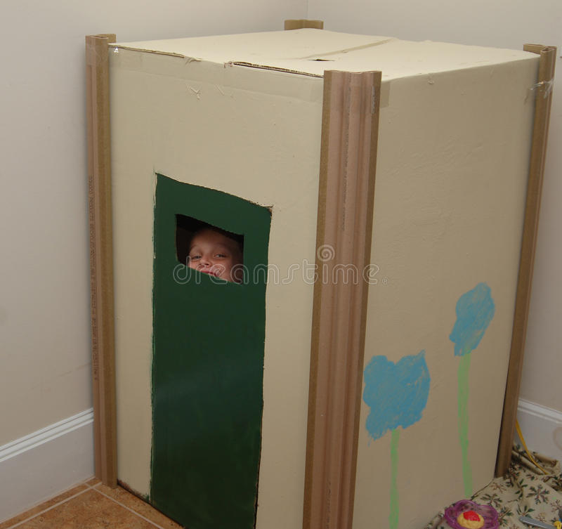 Box playhouse. Young boy looking through door of his large hand painted box playhouse royalty free stock photography