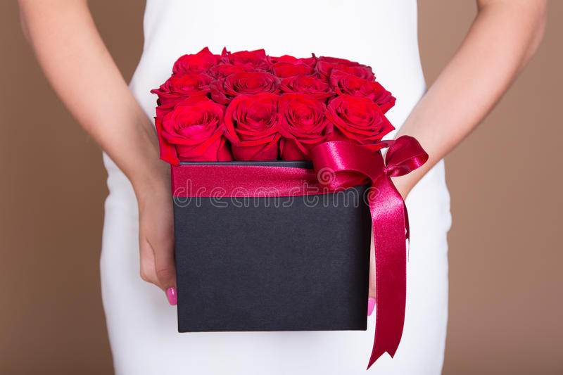 Box with red roses in female hands. Close up of box with red roses in female hands stock image