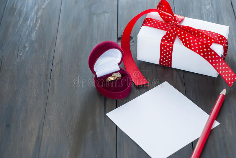 Box for rings and heart gift. Gift with red ribbon, heart box with a ring on Valentine`s Day royalty free stock photo