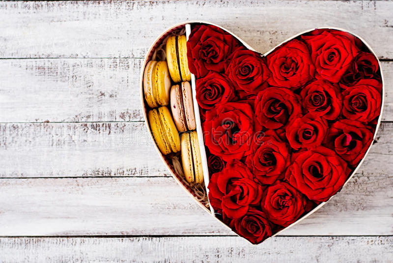 Box in the shape of a heart with red roses and macaroon. Gift on Valentine's Day. Top view royalty free stock photography