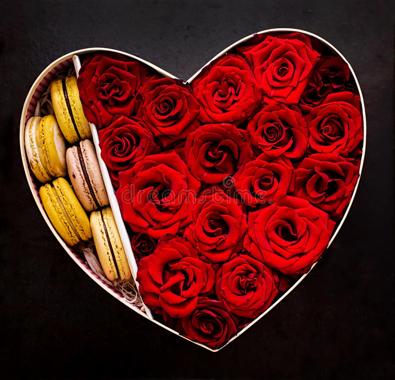 Box in the shape of a heart with red roses and macaroon. Gift on Valentine's Day. Top view stock photo