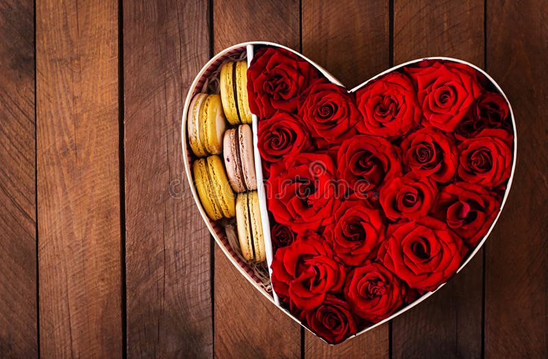 Box in the shape of a heart with red roses and macaroon. Gift on Valentine's Day. Top view stock photography