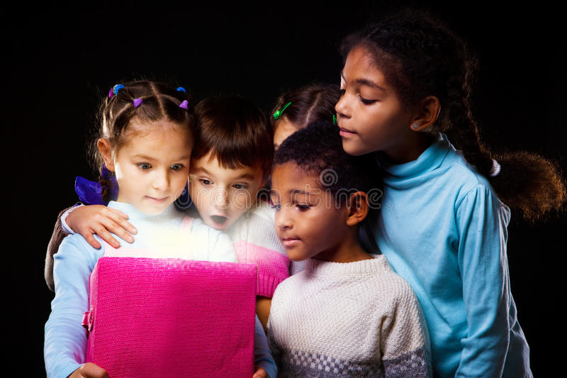 Box shining. Surprised children looking into the shining box stock photography