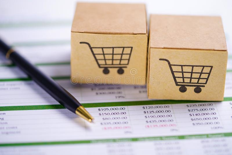 Box with shopping cart logo on spreadsheet paper with pen. stock image