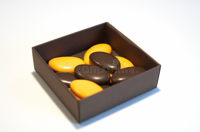 Box with sugared chocolates. Box on white background, brown and yellow sugared almonds and chocolates stock photos