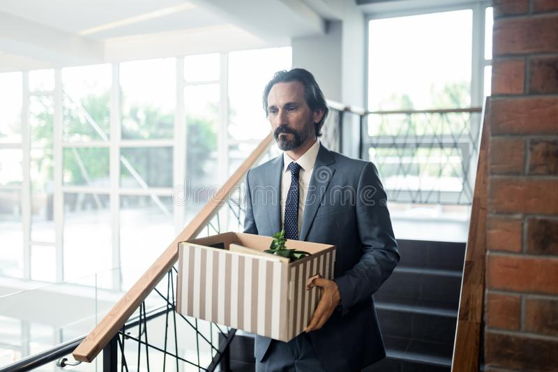 Office worker holding box with private things after been fired royalty free stock photography