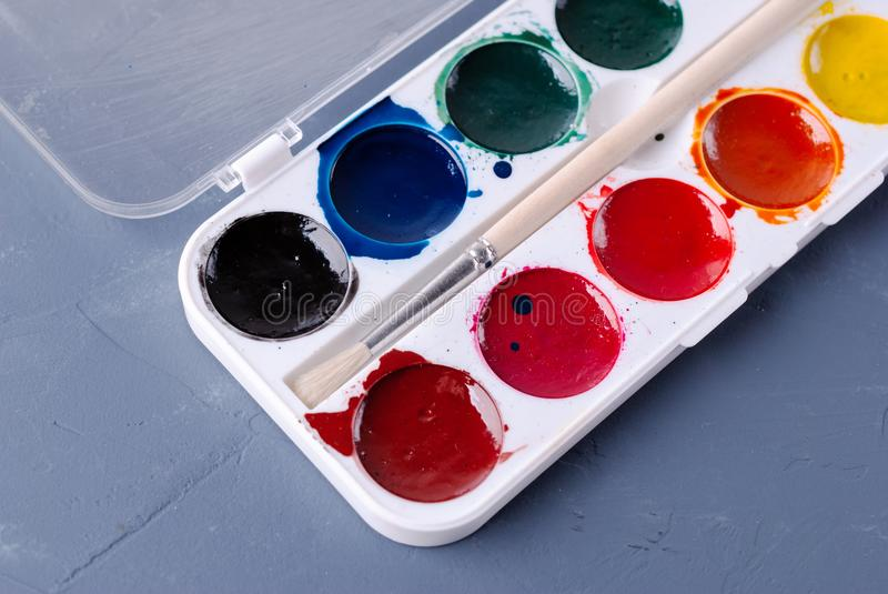 Box with used watercolor paints and a brush royalty free stock photography