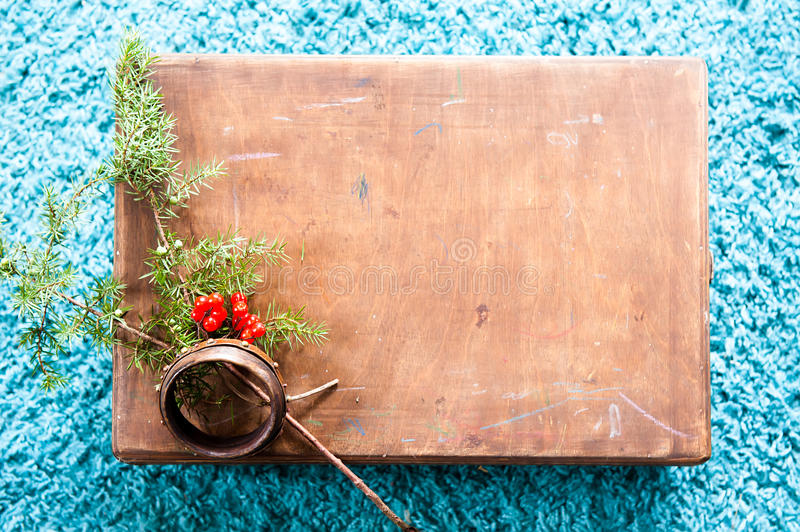 Box with wooden texture and fir tree on fluffy blue carpet background. Top view copy space royalty free stock images
