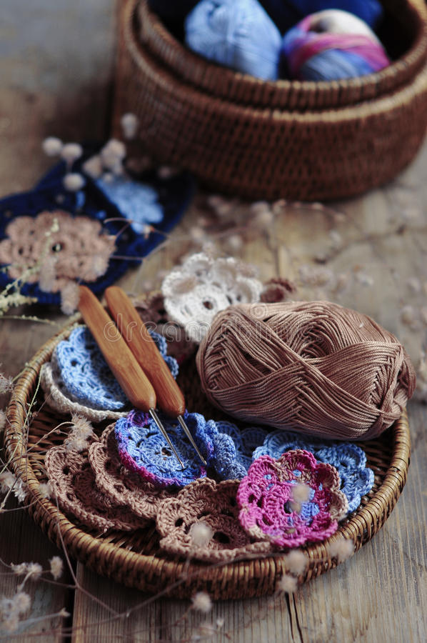 Box of yarn and crocheted flowers stock photography