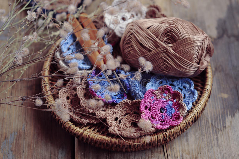 Box of yarn and crocheted flowers stock images