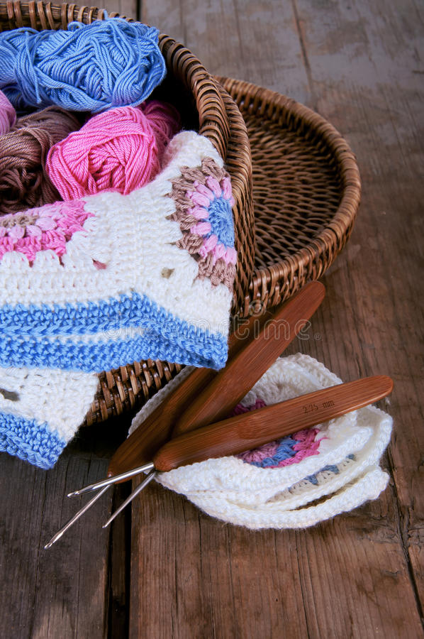 Box of yarn and granny square blanket with crochet hooks. Box of pink and blue yarn and granny square blanket with crochet hooks stock images