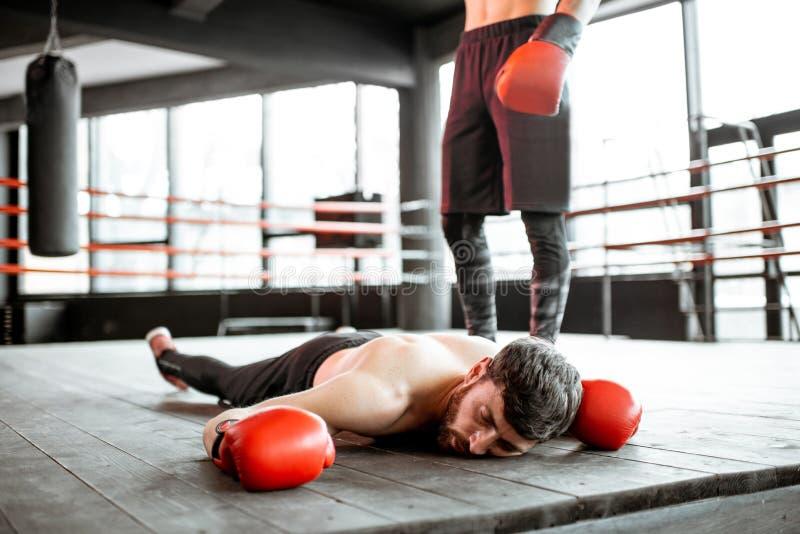 Boxare som faller på golvet under en boxas strid arkivbild