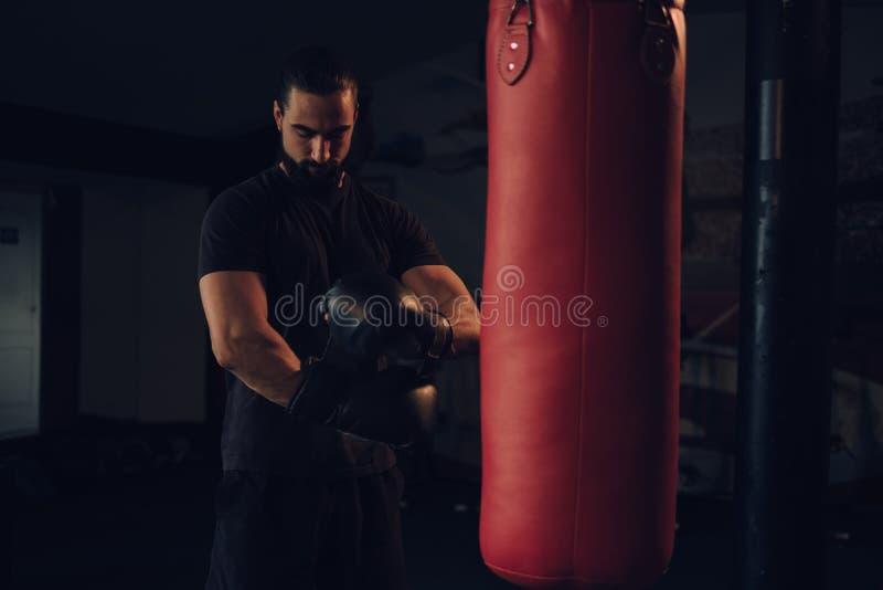 Boxare som sätter på handskar vid den tunga påsen arkivbild