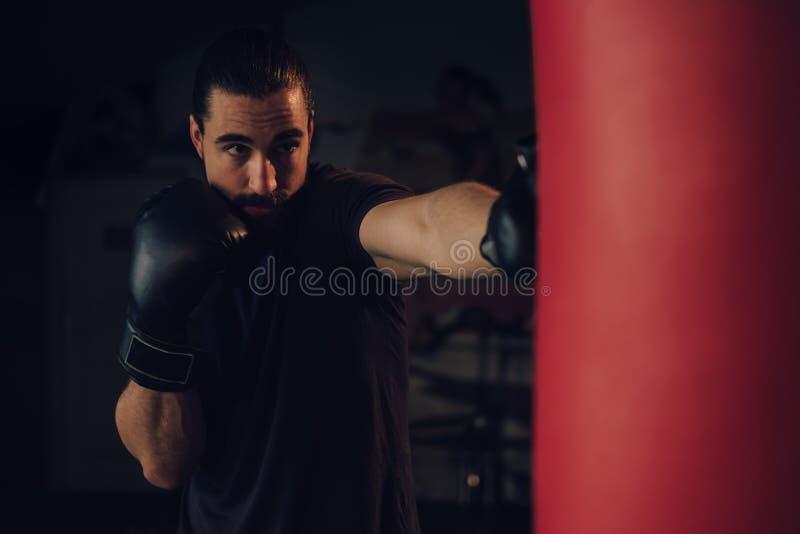 Boxare som slår den tunga påsen med den främre jaben arkivfoton
