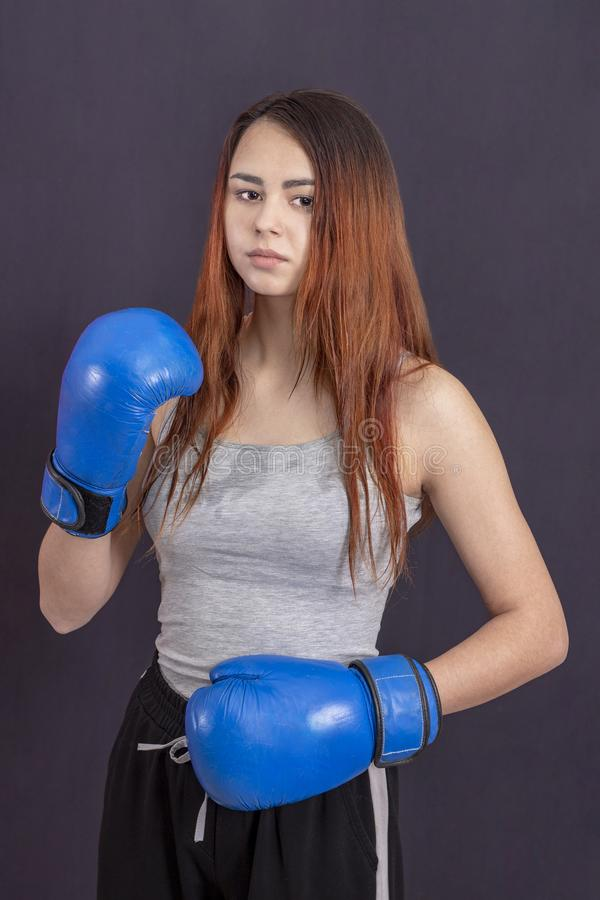 Boxareflicka i bl?a boxas handskar i en gr? t-skjorta i kugge arkivfoton
