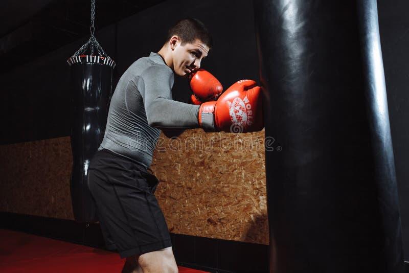 Boxaren slår en hastighetspåse i idrottshallen som utbildar chock royaltyfri bild