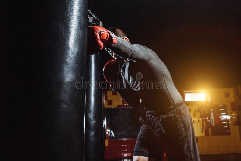 Boxaren slår en hastighetspåse i idrottshallen som utbildar chock royaltyfri fotografi