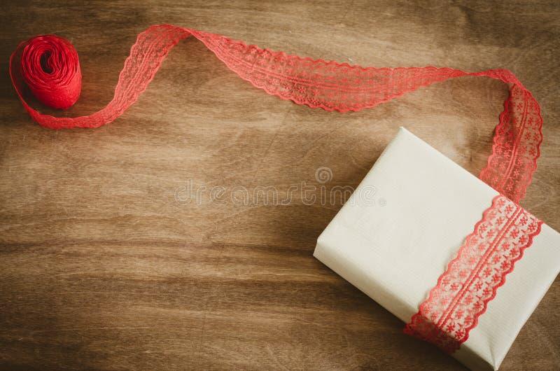 Boxe d'annata di Kraft con il regalo, legato con il nastro rosso su fondo di legno rustico fotografia stock libera da diritti
