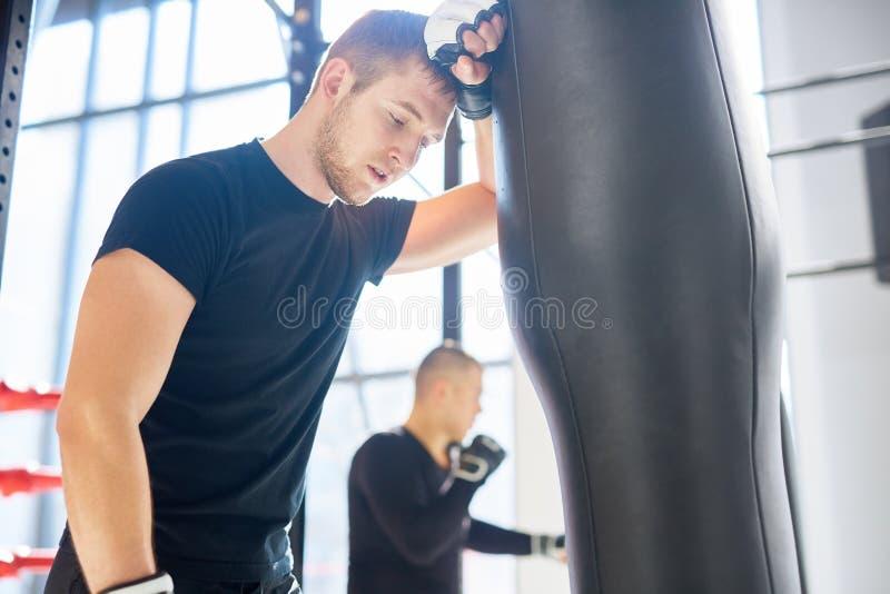 Boxeador agotado que se inclina en el saco de arena imágenes de archivo libres de regalías
