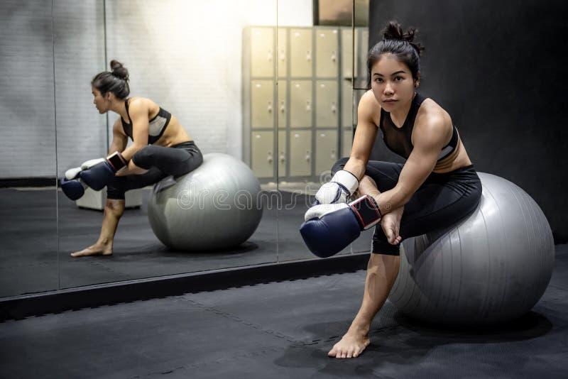 Boxeador asiático de la muchacha que se sienta en bola del ejercicio en gimnasio foto de archivo libre de regalías