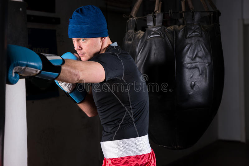 Boxeador atlético de sexo masculino con mirada severa en un sombrero y los guantes de boxeo t foto de archivo