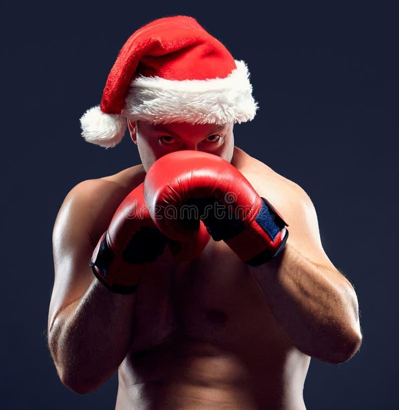 Boxeador de la aptitud de la Navidad que lleva el boxeo del sombrero de santa fotos de archivo libres de regalías
