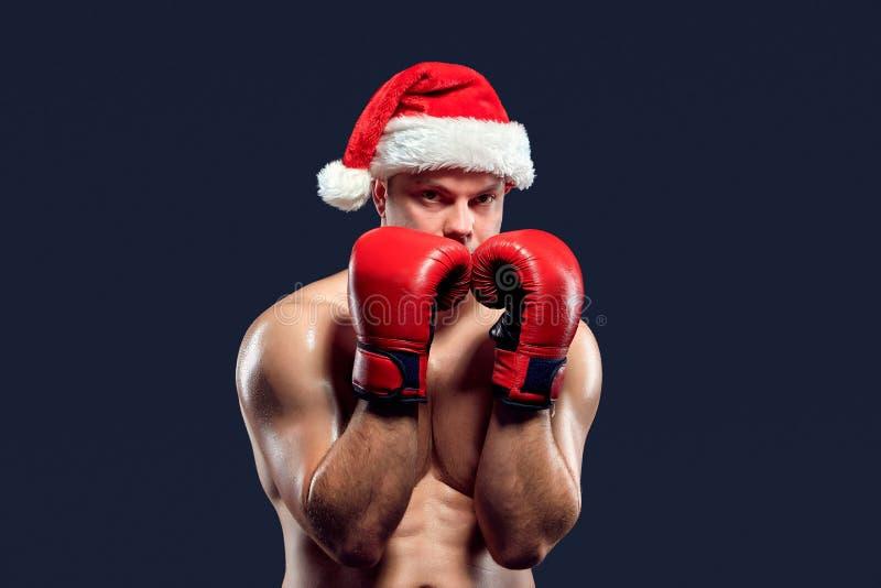 Boxeador de la aptitud de la Navidad que lleva el boxeo del sombrero de santa imágenes de archivo libres de regalías