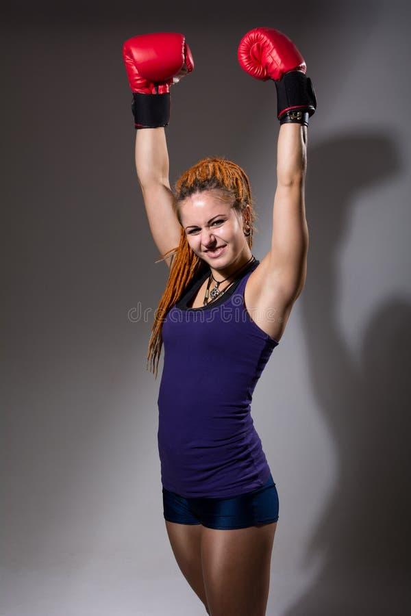 Boxeador de la mujer joven con los dreadlocks y los brazos aumentados fotografía de archivo
