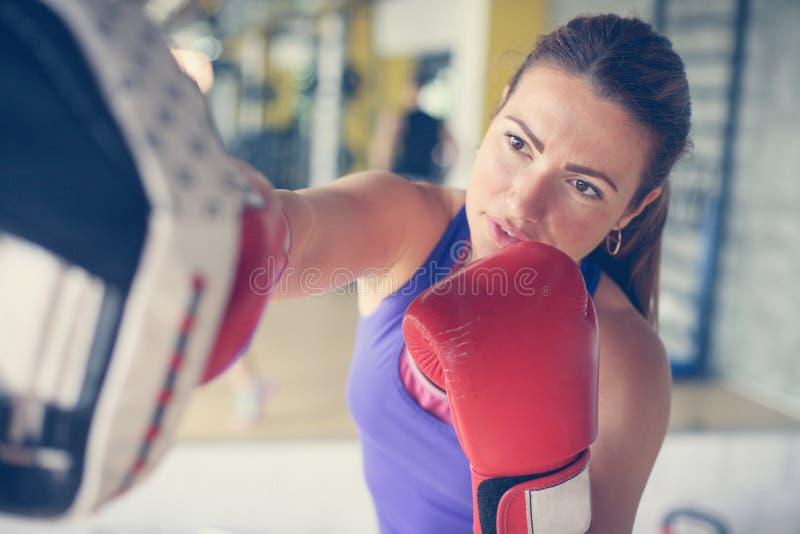 Boxeador de la mujer que golpea el guante de su compañero de entrenamiento imagen de archivo libre de regalías