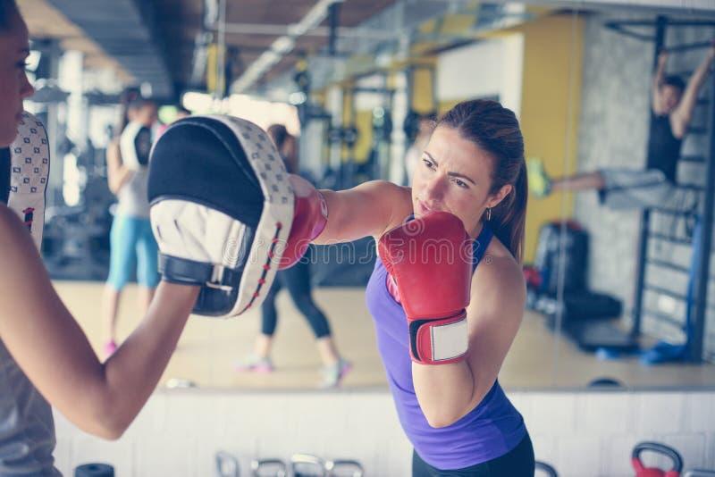 Boxeador de la mujer que golpea el guante de su compañero de entrenamiento Mujer wo foto de archivo libre de regalías