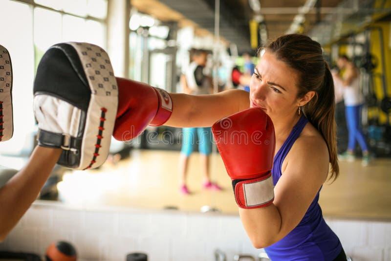 Boxeador de la mujer que golpea el guante de su compañero de entrenamiento Mujer wo imagen de archivo libre de regalías