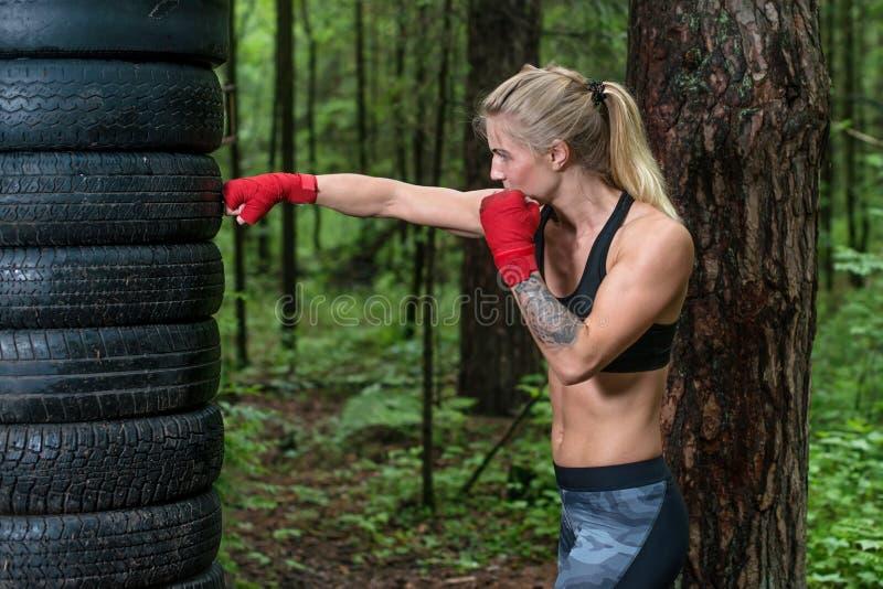 Boxeador de la mujer que hace el retroceso cruzado que se resuelve al aire libre imágenes de archivo libres de regalías