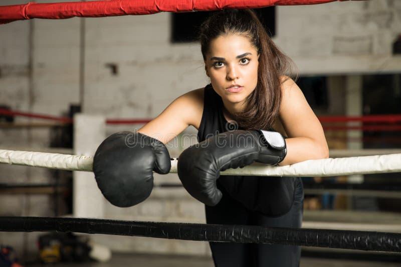 Boxeador de sexo femenino confiado en un ring de boxeo imagenes de archivo