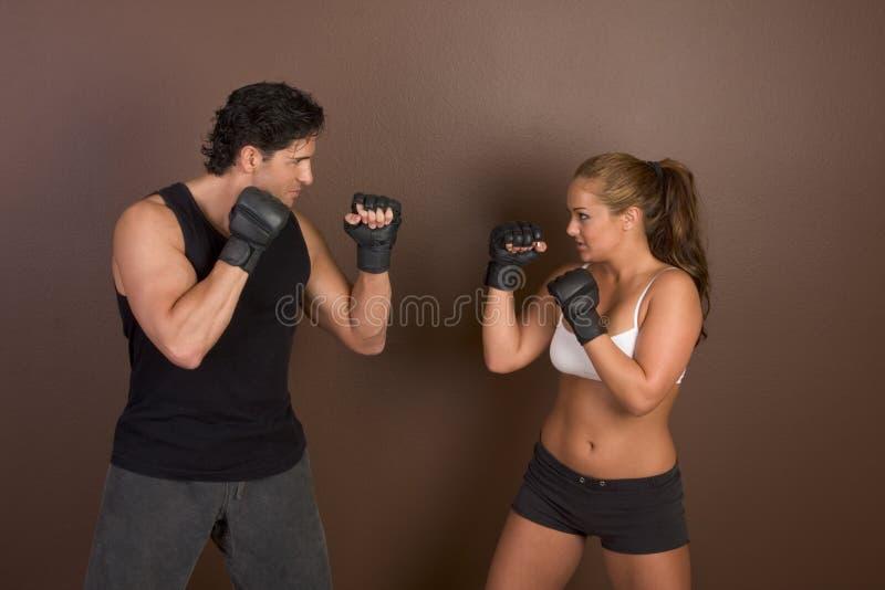 Boxeador de sexo femenino del retroceso con el amaestrador en entrenamiento sparring imagen de archivo libre de regalías