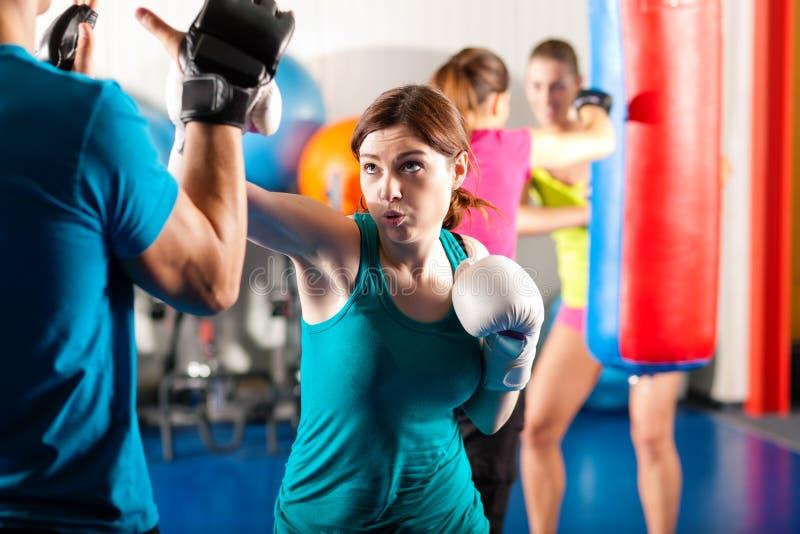 Boxeador de sexo femenino del retroceso con el amaestrador en sparring foto de archivo libre de regalías