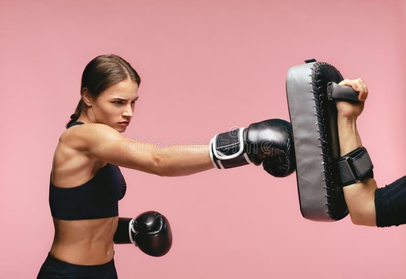 Boxeador de sexo femenino en guantes que entrena con los cojines del boxeo imagenes de archivo